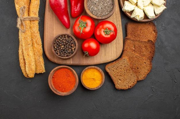 Widok z góry świeżych czerwonych pomidorów z przyprawami, serem i chlebem na czarno