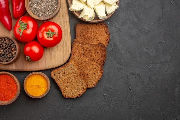 Widok z góry świeżych czerwonych pomidorów z przyprawami, serem i chlebem na czarnym stole