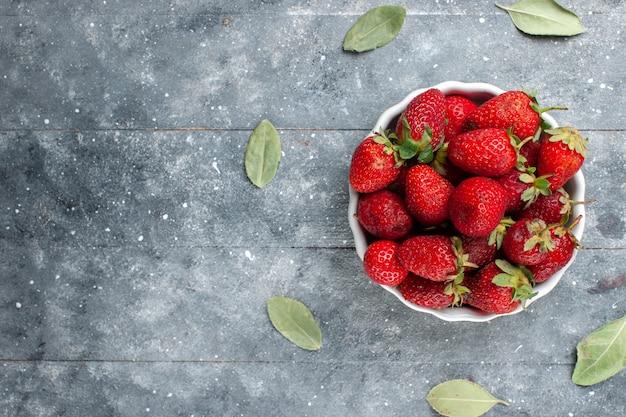 Widok z góry świeżych czerwonych truskawek wewnątrz białej tablicy wraz z zielonymi suszonymi liśćmi na szarej drewnianej, owocowej świeżej witaminie jagodowej