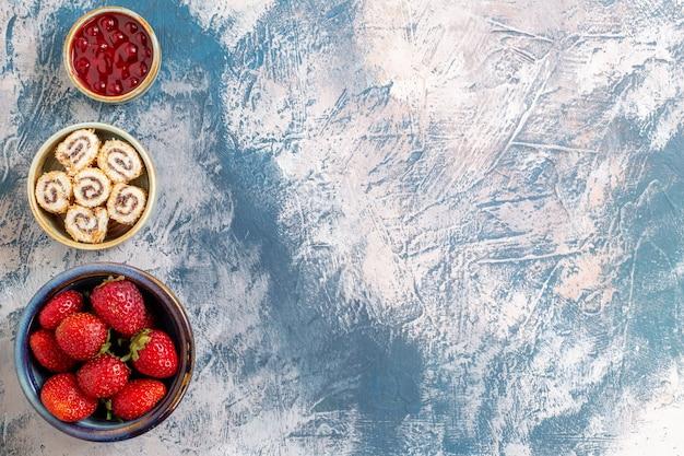 Widok z góry świeżych czerwonych truskawek z dżemem na jasnej powierzchni