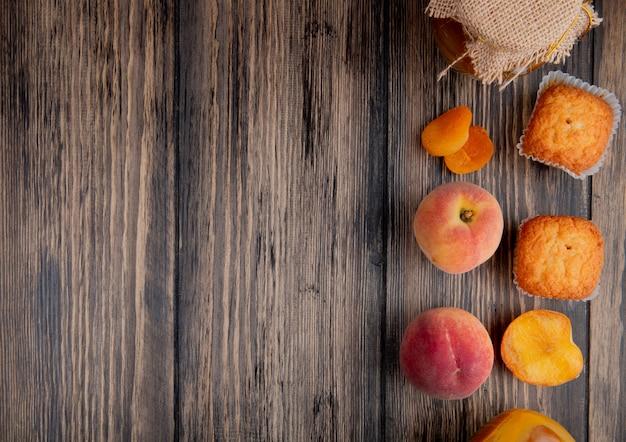 Widok z góry świeżych dojrzałych brzoskwiń z babeczki i dżem brzoskwiniowy w szklanym słoju na prosty drewniany stół z miejsca kopiowania