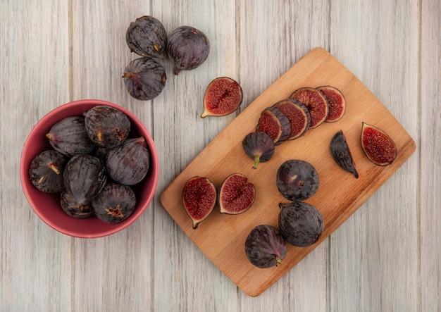 Widok z góry świeżych dojrzałych czarnych fig misyjnych na drewnianej desce kuchennej z czarnymi figami na misce na szarej powierzchni drewnianej