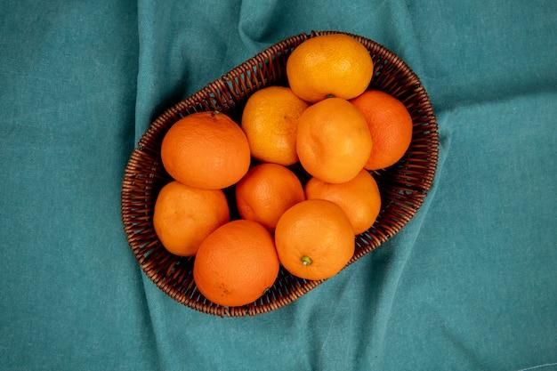 Widok z góry świeżych dojrzałych mandarynek w wiklinowym koszu na niebiesko