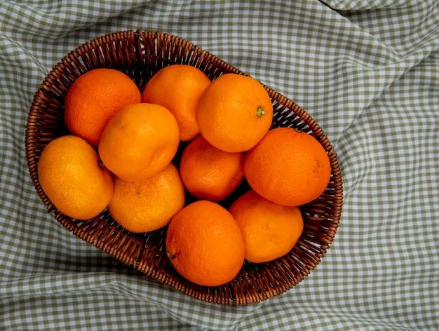 Widok z góry świeżych dojrzałych mandarynek w wiklinowym koszu na tkaninie w kratę