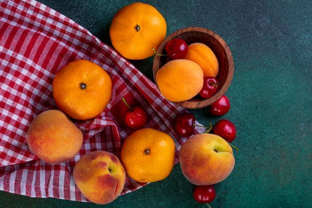 Widok z góry świeżych dojrzałych owoców mandarynki brzoskwinie z czerwonymi wiśniami na kraciastej tkaninie na ciemnozielonym