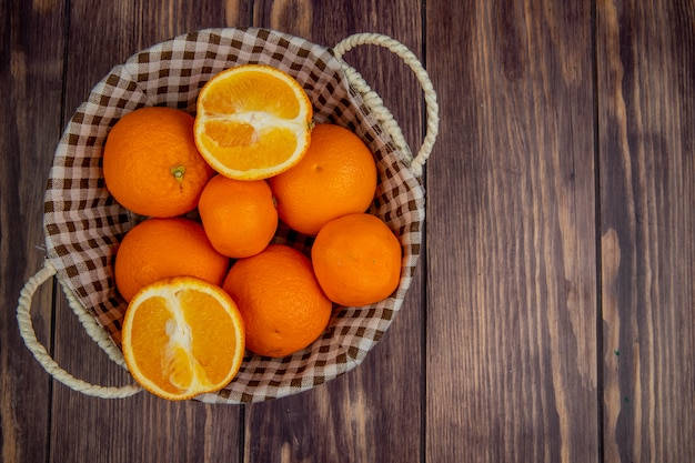 Widok z góry świeżych dojrzałych pomarańczy w wiklinowym koszu na rustykalnej drewnianej powierzchni z miejsca kopiowania