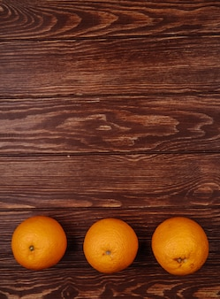 Widok z góry świeżych dojrzałych pomarańczy wyłożonych w rzędzie na drewnie z miejsca na kopię