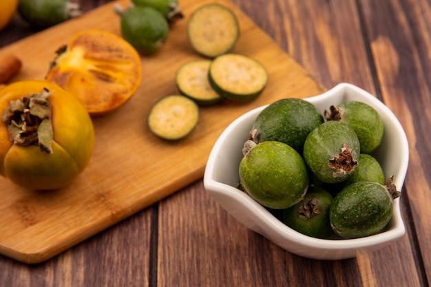 Widok z góry świeżych feijoas na misce z kawałkami feijoas z owocami persimmon na drewnianej desce kuchennej na drewnianej ścianie