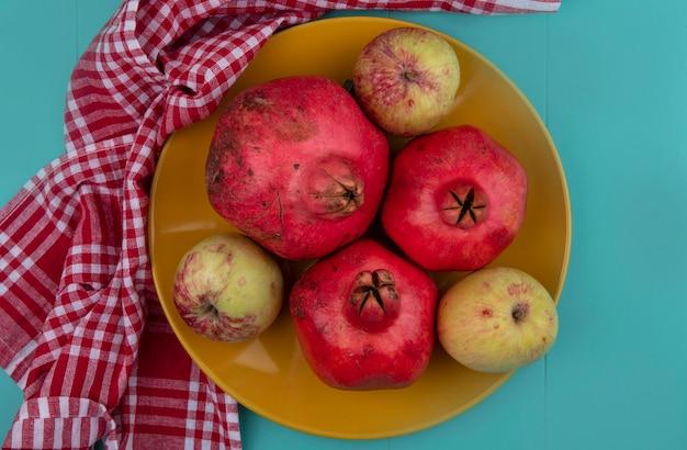 Widok z góry świeżych granatów na żółtym talerzu z jabłkami na sprawdzonej tablicy na niebieskim tle