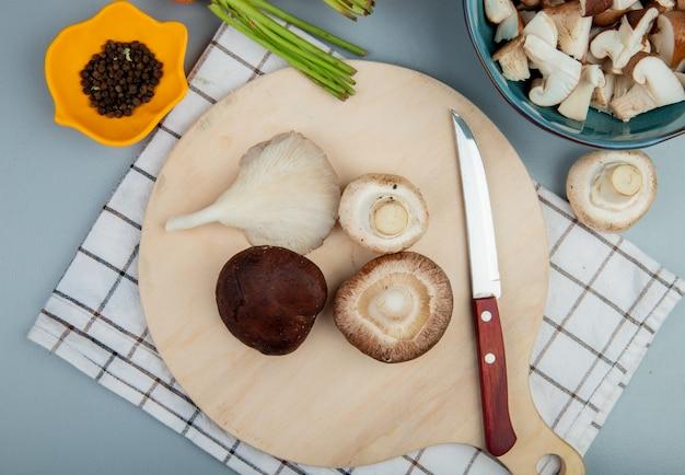 Widok z góry świeżych grzybów na drewnianej desce do krojenia z nożem kuchennym na jasnoniebieskim tle ze świeżą marchewką na jasnoniebieskim tle
