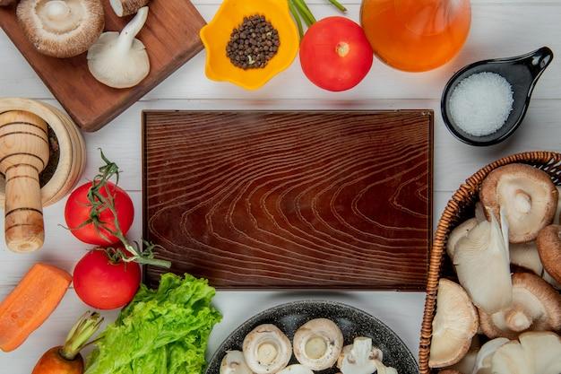 Widok z góry świeżych grzybów w wiklinowym koszu i pomidorów butelka oliwy z oliwek sól i ziarna pieprzu ułożone wokół drewnianej deski na białym