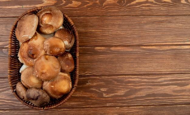 Widok z góry świeżych grzybów w wiklinowym koszu na drewnie rustykalnym z miejsca na kopię