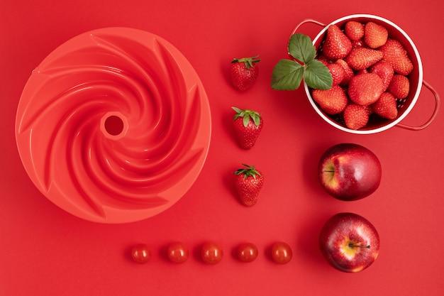 Widok z góry świeżych i soczystych owoców słonecznika i przyborów kuchennych na czerwonej ścianie. lato, czerwone owoce, witaminy, gotowanie, koncepcja ekologicznych jagód. leżał płasko, kopia przestrzeń