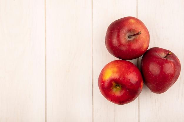 Widok z góry świeżych jabłek czerwonych na białym tle na białej powierzchni drewnianych z miejsca na kopię
