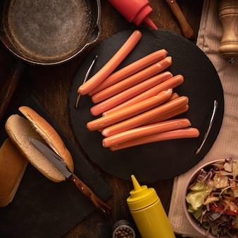 Widok z góry świeżych kiełbas na hot dogi w ciemności z bułkami.