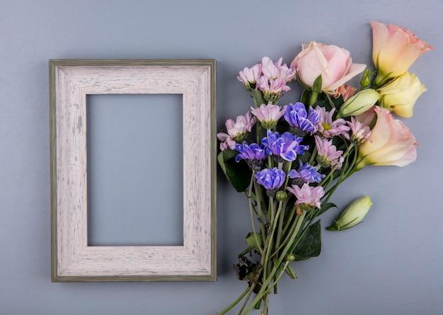 Widok z góry świeżych kwiatów, takich jak róża stokrotka na białym tle na szarym tle z miejsca na kopię