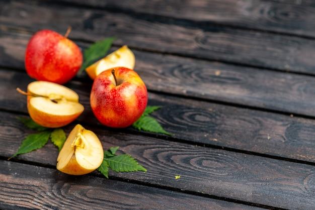 Widok z góry świeżych, naturalnych posiekanych i całych czerwonych jabłek i liści na czarnym tle