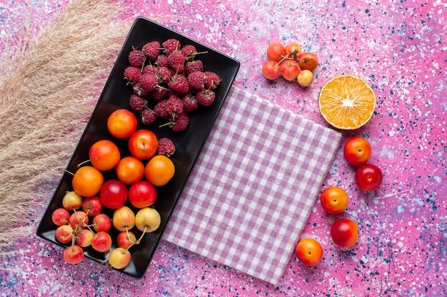 Widok z góry świeżych owoców malin i śliwek wewnątrz czarnej formy na różowej powierzchni