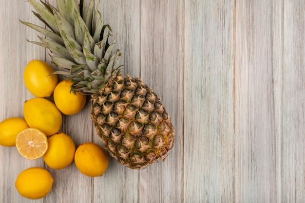 Widok z góry świeżych owoców, takich jak ananas i cytryny, na białym tle na szarej drewnianej ścianie z miejsca na kopię
