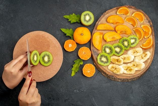 Widok z góry świeżych owoców ustawionych na drewnianej tacy i ręczne siekanie kiwi na desce do krojenia na czarnej powierzchni