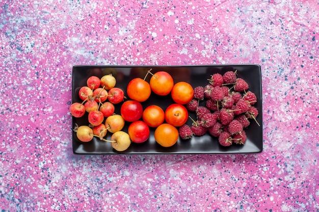 Widok z góry świeżych owoców wewnątrz czarnej formy na różowej powierzchni