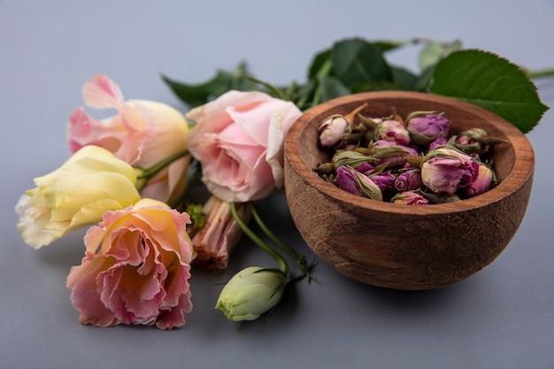 Widok z góry świeżych pąków róży na drewnianej misce ze świeżych liści na szarym tle