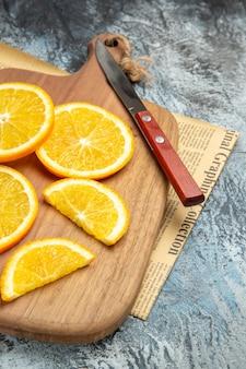 Widok z góry świeżych plasterków cytryny z nożem na drewnianej desce do krojenia na gazecie po prawej stronie szarego tła