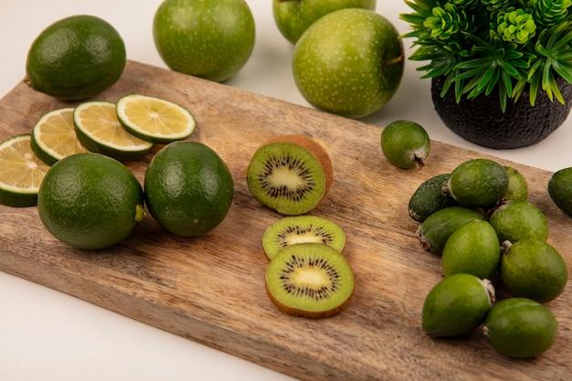 Widok z góry świeżych plasterków limonki na drewnianej desce kuchennej z kiwi feijoa i zielonymi jabłkami na białym tle