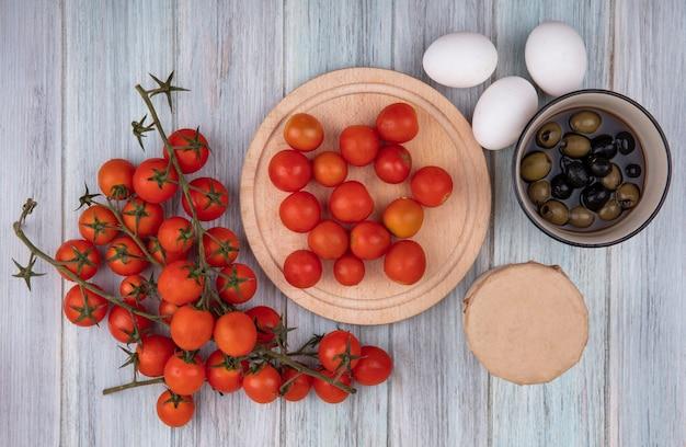 Widok z góry świeżych pomidorów z czerwonej winorośli na miskę z pomidorami odizolowanymi na drewnianej desce kuchennej z oliwkami na misce i jajkami na szarym tle drewnianych