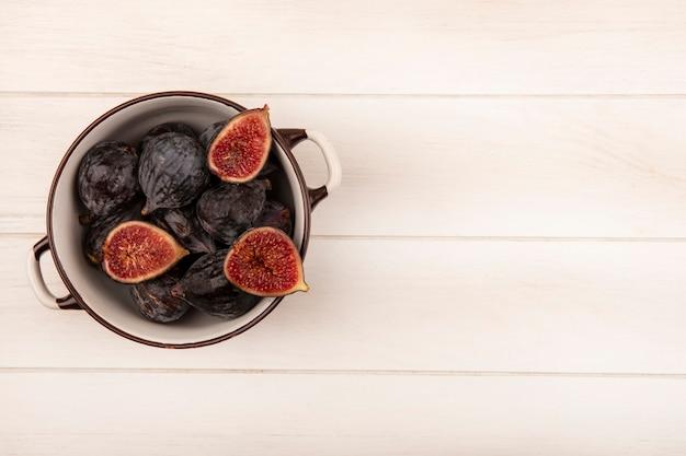 Widok z góry świeżych słodkich czarnych fig misyjnych na misce na białej powierzchni drewnianej z miejsca na kopię