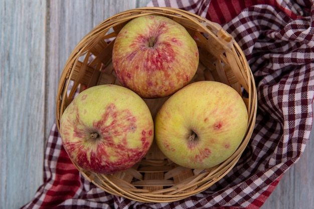 Widok z góry świeżych soczystych jabłek na wiadrze na kratkę na szarym tle