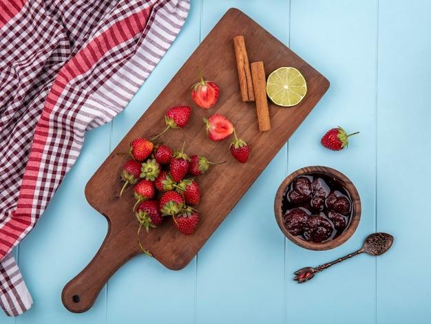 Widok z góry świeżych truskawek na drewnianej desce kuchennej z laskami cynamonu z dżemem truskawkowym na niebieskim tle