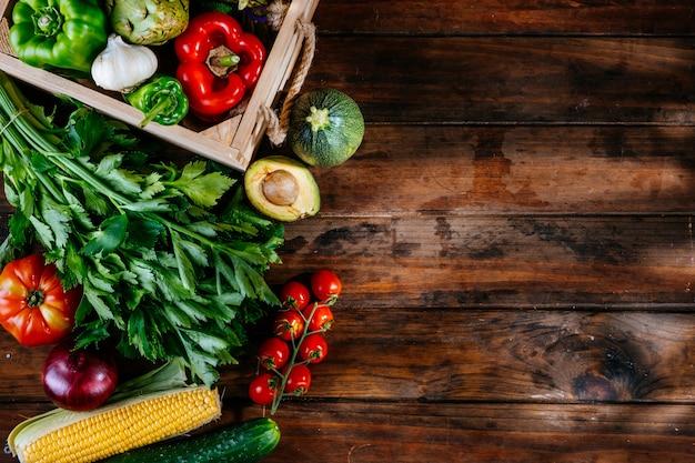 Widok z góry świeżych warzyw na drewnianym stole, zbilansowana dieta, wolne miejsce na logo