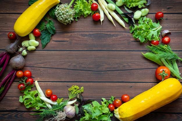 Widok z góry świeżych warzyw umieszczonych w kręgu na tle drewnianego stołu z miejscem na kopię