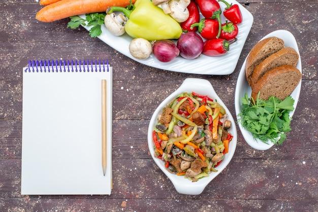 Widok z góry świeżych warzyw z grzybami wewnątrz płyty z bochenkami chleba i notatnikiem zieleni na brązowy, warzywny posiłek grzybowy