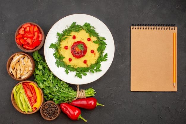 Widok z góry świeżych warzyw z zieleniną i daniem ziemniaczanym na czarno