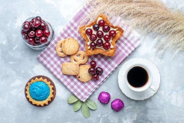 Widok z góry świeżych wiśni na talerzu z kremową herbatą w kształcie gwiazdy i ciasteczkami na lekkim, kwaśnym ciastku owocowym