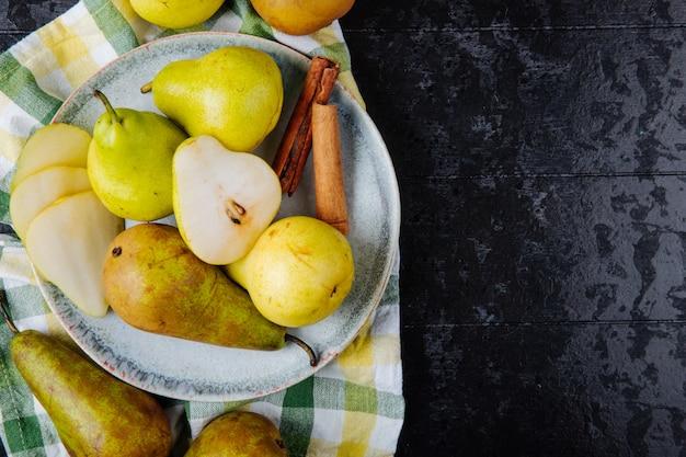 Widok z góry świeżych zielonych gruszek i połówek gruszki na talerzu na kraciastym obrusie na czarnym tle z miejsca kopiowania