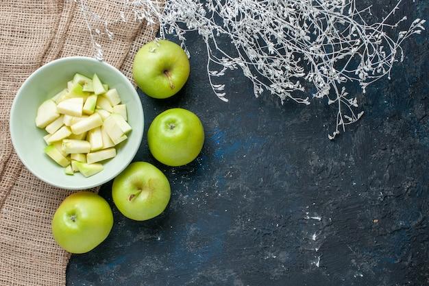 Widok z góry świeżych zielonych jabłek łagodny i soczysty z pokrojonym jabłkiem wewnątrz talerza na ciemnoniebieskim, owoce świeża żywność zdrowie witamina