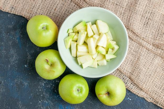 Widok z góry świeżych zielonych jabłek, soczystych i soczystych z pokrojonym jabłkiem wewnątrz talerza na ciemnym biurku, owoce świeże witamina zdrowia żywności