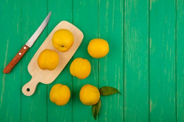 Widok z góry świeżych żółtych brzoskwiń na drewnianej desce kuchennej z nożem z brzoskwiniami na białym tle na zielonym tle drewnianych