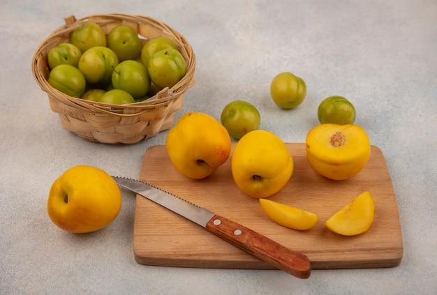 Widok z góry świeżych żółtych brzoskwiń na drewnianej desce kuchennej z nożem z zielonymi śliwkami wiśniowymi na wiadrze na białym tle