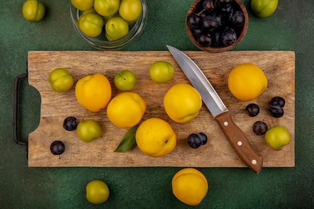 Widok z góry świeżych żółtych brzoskwiń na drewnianej desce kuchennej z zielonymi śliwkami wiśniowymi z nożem z tarniną na drewnianej misce na zielonym tle