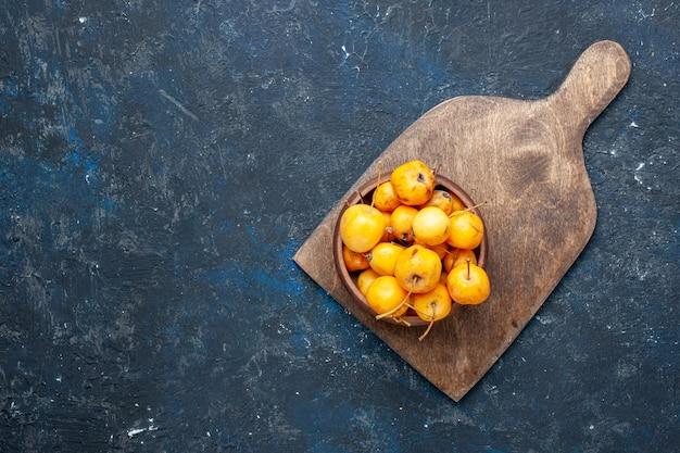 Widok z góry świeżych żółtych wiśni dojrzałych słodkich owoców na ciemnych, łagodnych owocowych świeżych czereśni