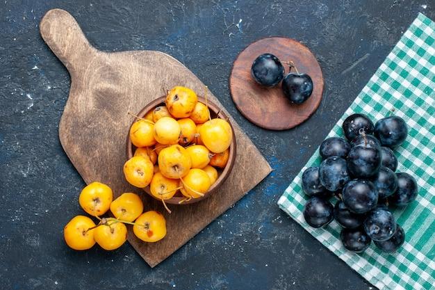 Widok z góry świeżych żółtych wiśni, dojrzałych słodkich owoców z tarniną na szaro-ciemnym biurku, łagodny owoc świeżej czereśni