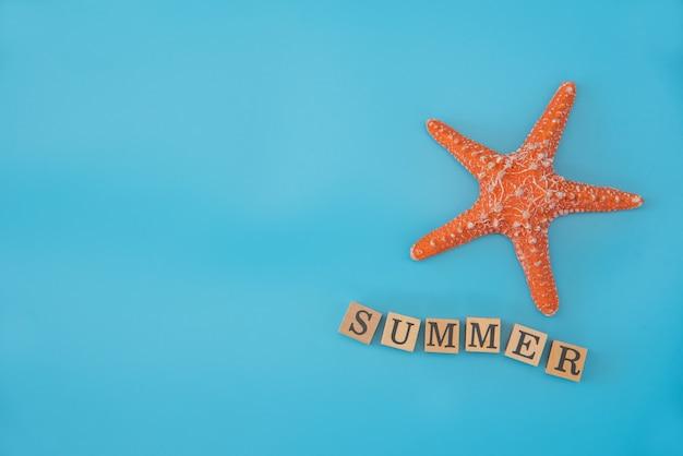 """Widok z góry symulowana rozgwiazda i słowo """"summer"""" umieszczone na niebieskim tle koncepcji letnich podróży"""