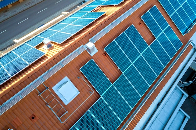 Widok z góry systemu paneli fotowoltaicznych w kolorze niebieskim na dachu budynku mieszkalnego. odnawialna produkcja ekologicznej zielonej energii.