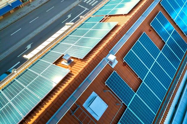Widok z góry systemu paneli fotowoltaicznych w kolorze niebieskim na dachu budynku mieszkalnego.