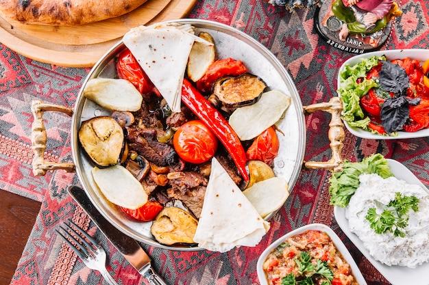 Widok z góry szałwia mięsna z pomidorami chleb pita i sałatkami na stole