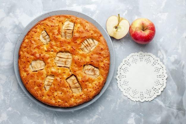 Widok z góry szarlotka wewnątrz płyty ze świeżych jabłek na jasnym tle ciasto cukrowe biszkoptowe słodkie wypieki